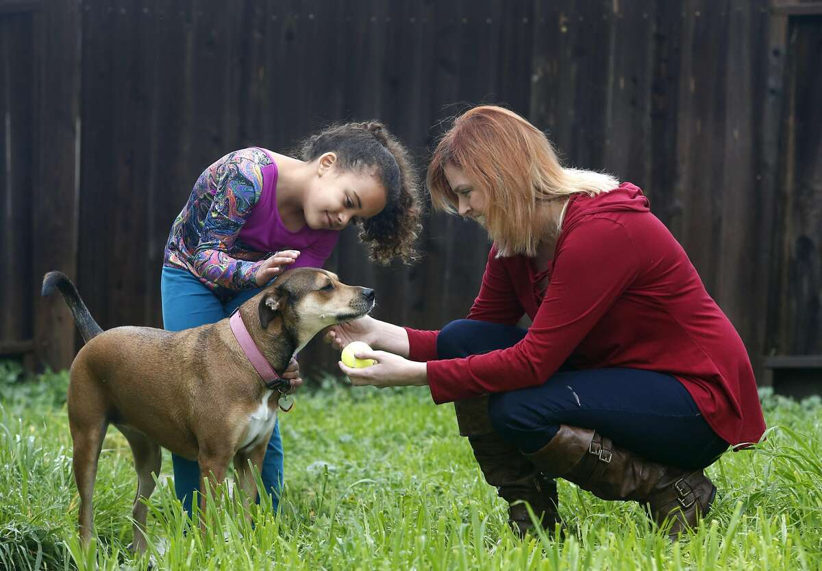 Heather Jacoby and her 7-year-old daughter Billie pets Jazzie, the family dog, at their home in Vacaville, Calif. on Saturday, Feb. 4, 2017. Jacoby isn't thrilled with the prospect that Planned Parenthood, where she's received medical treatment in the past, could be defunded by the Trump Administration.