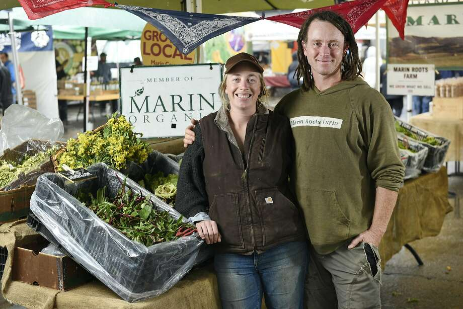 Moira and Jesse Kuhn of Marin Roots Farm at their booth at the Ferry Plaza Farmers Market in S.F. Photo: Michael Short, Special To The Chronicle