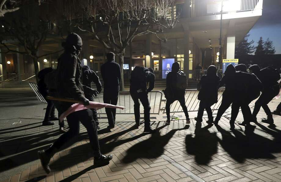 Masked protesters tear down security fences surrounding the site of a planned appearance by right-wing commentator Milo Yiannopoulos on Wednesday night at UC Berkeley. Photo: Scott Strazzante / Scott Strazzante / The Chronicle / **MANDATORY CREDIT FOR PHOTOG AND SF CHRONICLE/NO SALES/MAGS OUT/TV