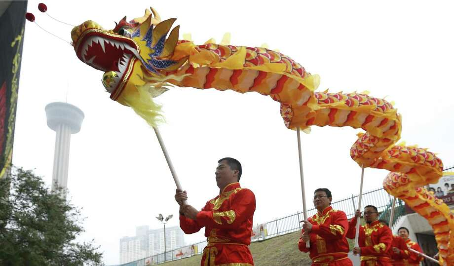 """Members of the San Antonio Chinese Dragon Dance Team join in a mini-parade as the Institute of Texan Cultures hosts the 2017 Asian Festival on Saturday, Feb. 4, 2017. In conjunction with the Asian New Year, ITC marked a milestone of 30 years hosting the festival. Guests were treated to various types of Asian foods, cultural performances and even """"Mah Jong"""" - a game similar to the card game, Bridge, - that is played on tiles on felt table. Attendance was steady despite cooler temperatures and a light mist. UTSA President Ricardo Romo helped kick off the event with the lighting of a long strand of firecrackers before leading Chinese lion and dragon dancers with a mini-parade to start off the celebration. (Kin Man Hui/San Antonio Express-News) Photo: Kin Man Hui, Staff / San Antonio Express-News / ©2017 San Antonio Express-News"""