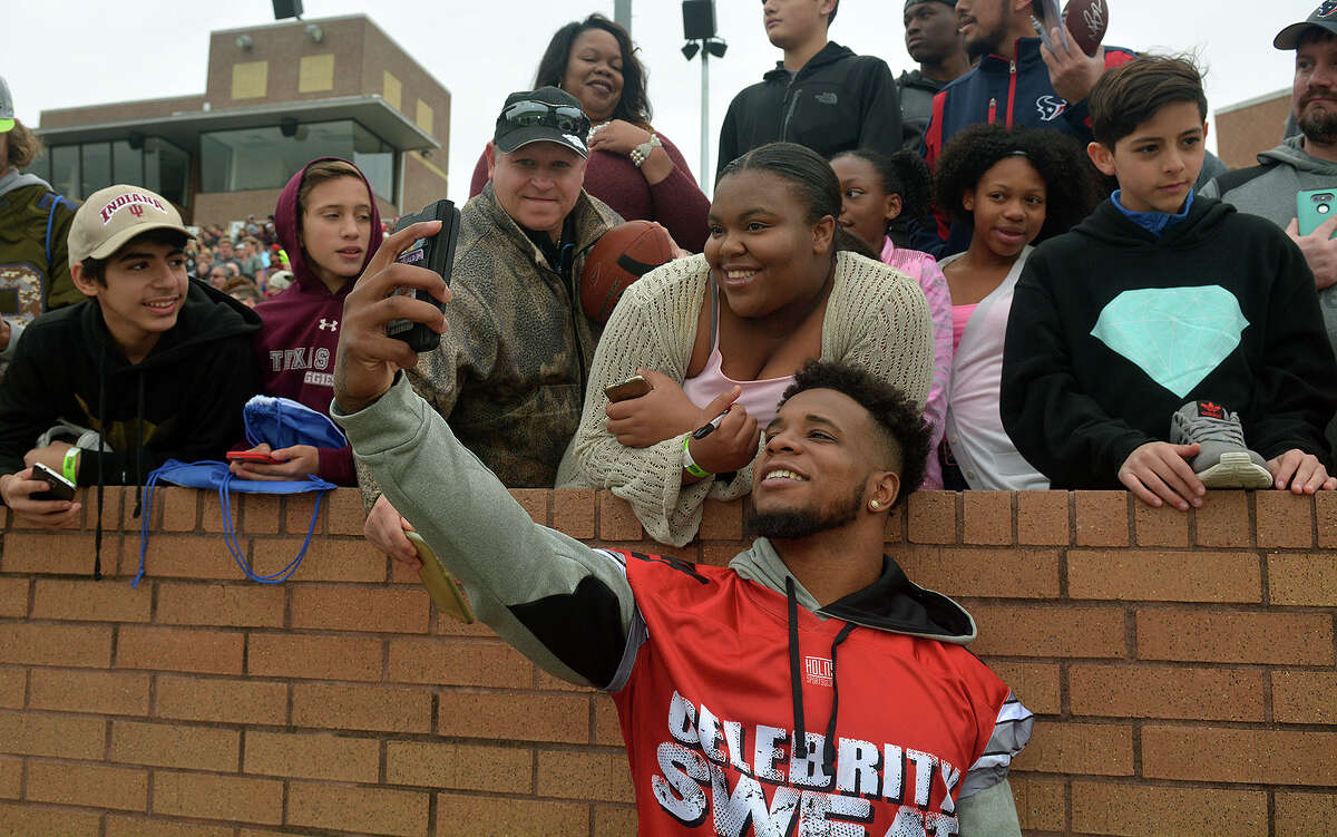 Kayle Ward, center, of Katy, gets a selfie with a Team Cousins player during the Celebrity Flag Football Challenge at Rhodes Stadium in Katy on Saturday, Feb. 4, 2017. (Photo by Jerry Baker/Freelance)