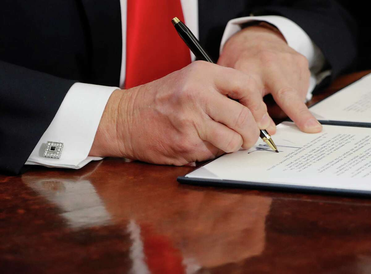 In this Feb. 3, 2017, photo, President Donald Trump signs an executive order in the Oval Office of the White House in Washington. (AP Photo/Pablo Martinez Monsivais)