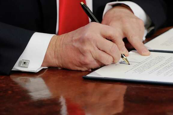 In this Feb. 3, 2017, photo, President Donald Trump signs an executive order in the Oval Office of the White House in Washington. Reality took a beating from the Washington blame game this past week. Americans heard about a Kentucky massacre that never happened, a travel ban that was a ban despite it being called something else, and a dark plot to help Russian intelligence that was nothing of the sort. (AP Photo/Pablo Martinez Monsivais)