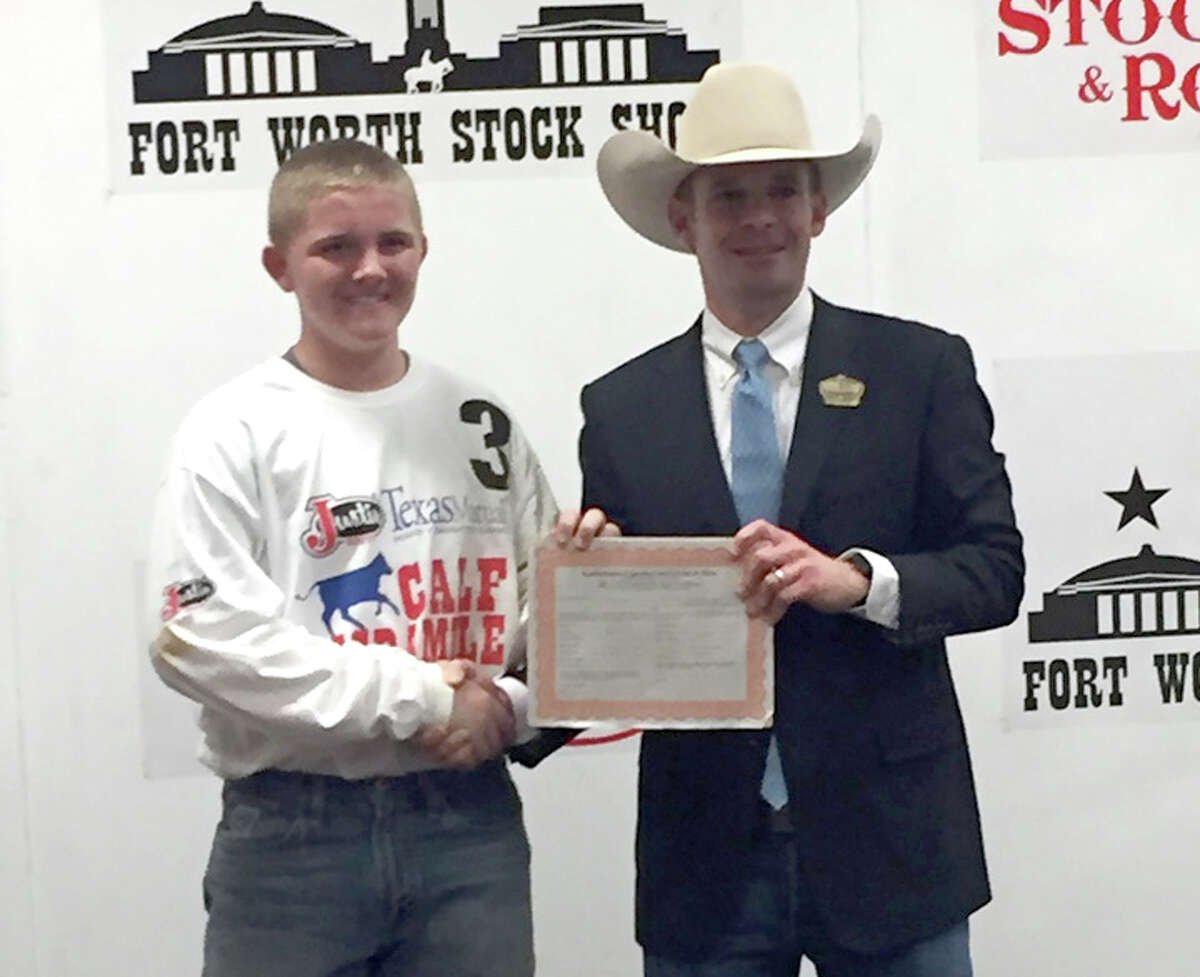Coldspring FFA member Bret Carter is presented his award for catching a calf in the Fort Worth Stock Show Calf Scramble.