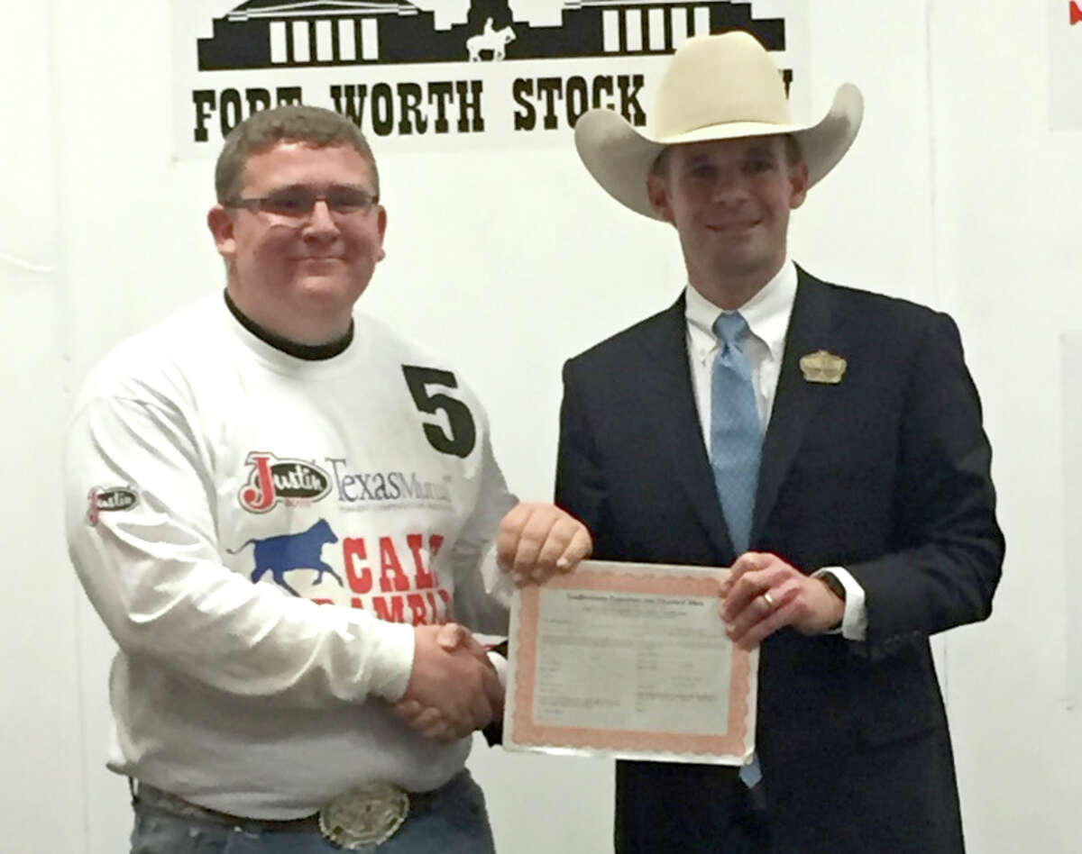 Coldspring FFA member Garrett Richardson is presented his award for catching a calf in the Fort Worth Stock Show Calf Scramble.
