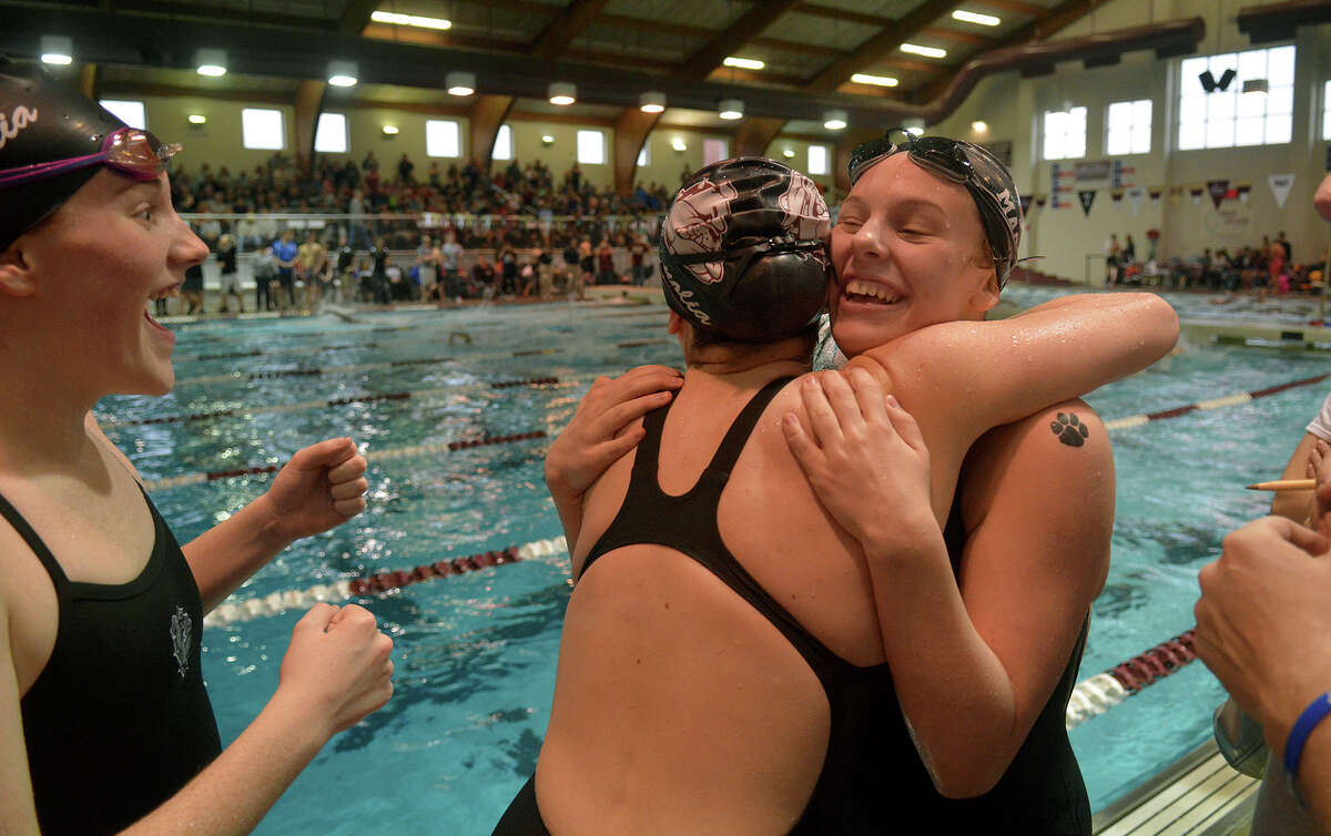 Magnolia sophomore Kiley Moriarty, right, hugs senior Caitlin Clements, center, while Caitlin's sister Carley, left, a freshman, waits for her hug after Caitlin won the Girls 100 Yard Freestyle while at the Region 6-5A Swimming & Diving Championships at the Michael D. Holland Aquatic Center in Magnolia on Saturday, Feb. 4, 2017. (Photo by Jerry Baker)
