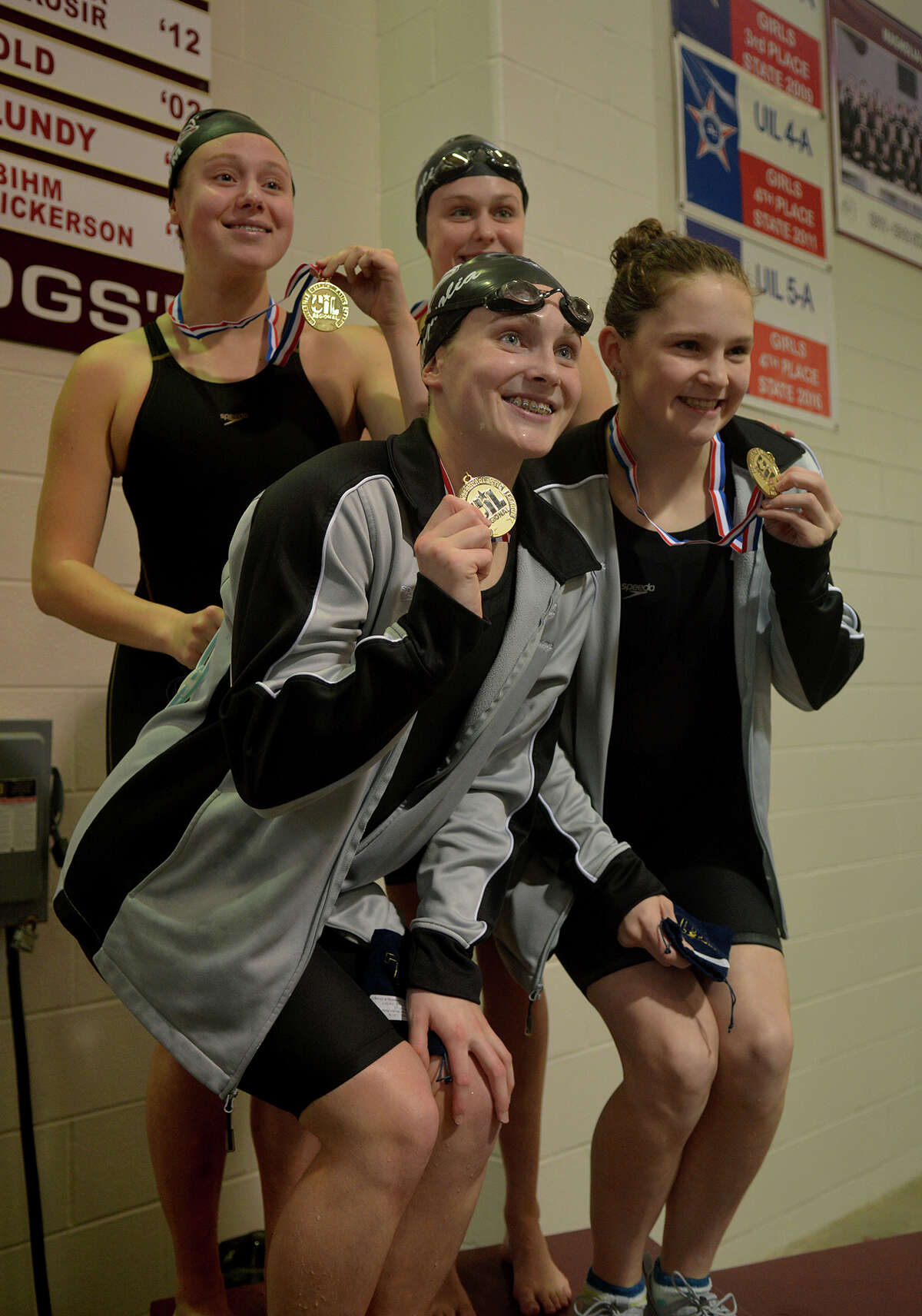 The Magnolia High School Girls Medley Relay, including senior Caitlin Clements, clockwise from bottom left, senior Dove Niccum, sophomore Savannah Schwienteck, and freshman Olivia Gonder, show off their gold medals after winning their event at the 2017 Region 6-5A Swimming & Diving Championships at the Michael D. Holland Aquatic Center in Magnolia on Saturday, Feb. 4, 2017. (Photo by Jerry Baker)