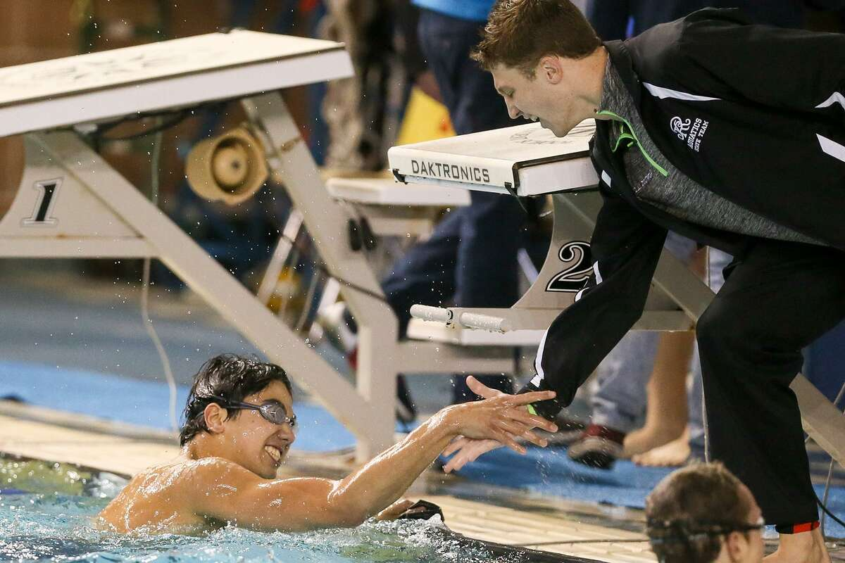 Reagan's Brandon Garcia (left) is congratulated after winning the boys 100-yard freestyle during the Region VII-6A swimming championships at Davis Natatorium on Feb. 4, 2017.