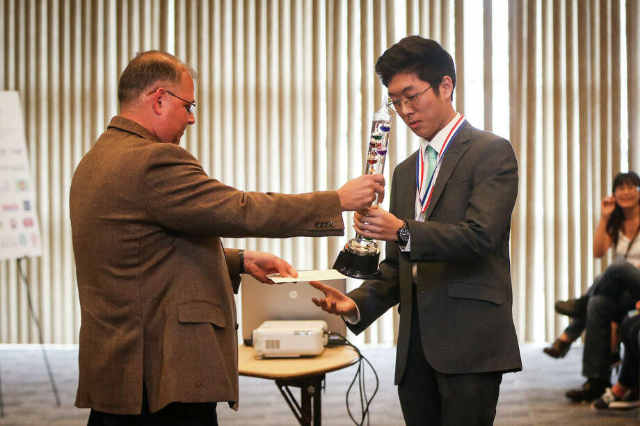 Andy Kim, 17, places first in the top category during the SCI://TECH Exposition's Senior High Science Fair, with the award presented by Mike Papadimitriou, Headmaster of the Academy for Science and Health Professions, on Saturday, Feb. 4, 2017, at The Lone Star Convention Center. Photo: Michael Minasi, Staff Photographer / © 2017 Houston Chronicle