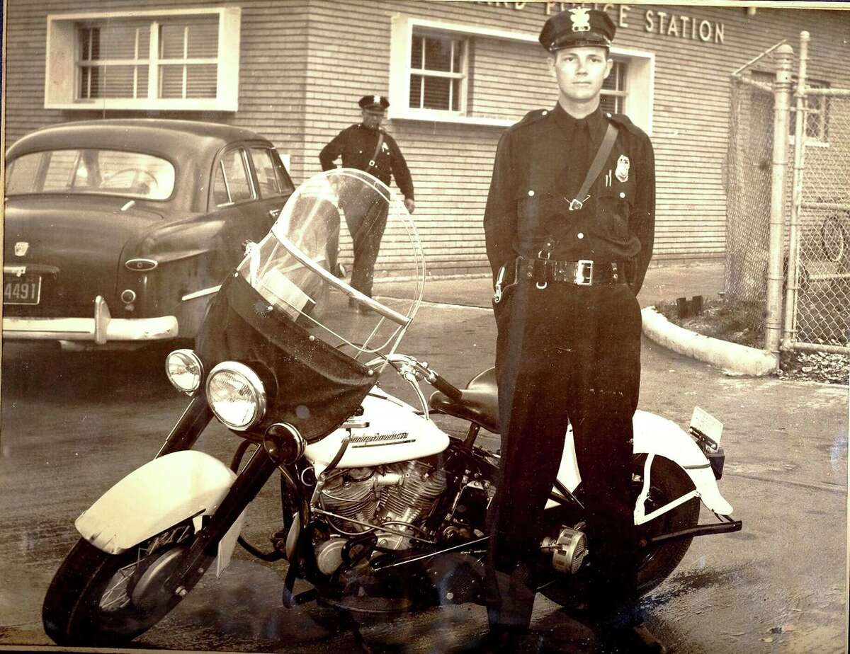 Officer Doug Warren with a Harley Davidson motorcycle in the 1950s.