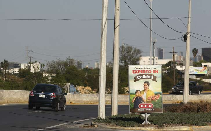 H-E-B store signs are placed along a road in Monterrey, Mexico, Thursday, March 13, 2014. H-E-B is in a heated battle for customers with Walmart in the north estern part of Mexico.