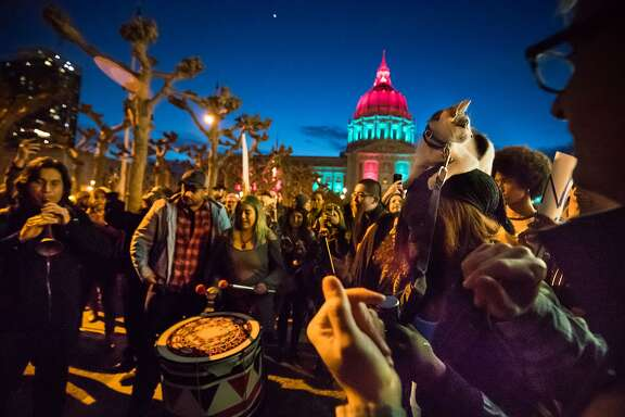 Calvin Lai on the zurna and Fabiola Danielle Quiroz on a large drum play to participants after the rally, including Mioshia Syon's cat Mafia on Saturday, Feb. 4, 2017 in San Francisco, CA  Protest against trump plan for wall on Mexican border and ban on immigrants and visitors from a number of mainly Muslim countries at the Civic Center Plaza.  Organizers are calling it a peaceful protest expected to draw more than 6,000 people.