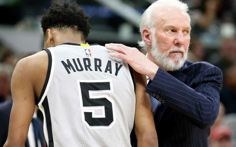 Gregg Popovich greets guard Dejounte Murray as returns to the bench. Photo: Edward A. Ornelas /San Antonio Express-News / © 2017 San Antonio Express-News