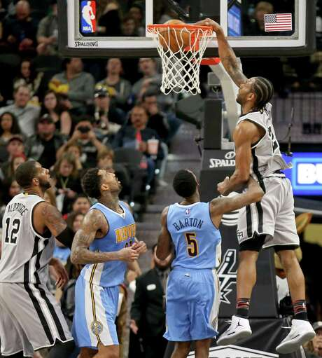 San Antonio Spurs' Kawhi Leonard dunks over Denver NuggetsÕ Will Barton as San Antonio Spurs' LaMarcus Aldridge (from left) and Denver NuggetsÕ Wilson Chandler look on during second half action Saturday Feb. 4, 2017 at the AT&T Center. The Spurs won 121-97. Photo: Edward A. Ornelas, Staff / San Antonio Express-News / © 2017 San Antonio Express-News