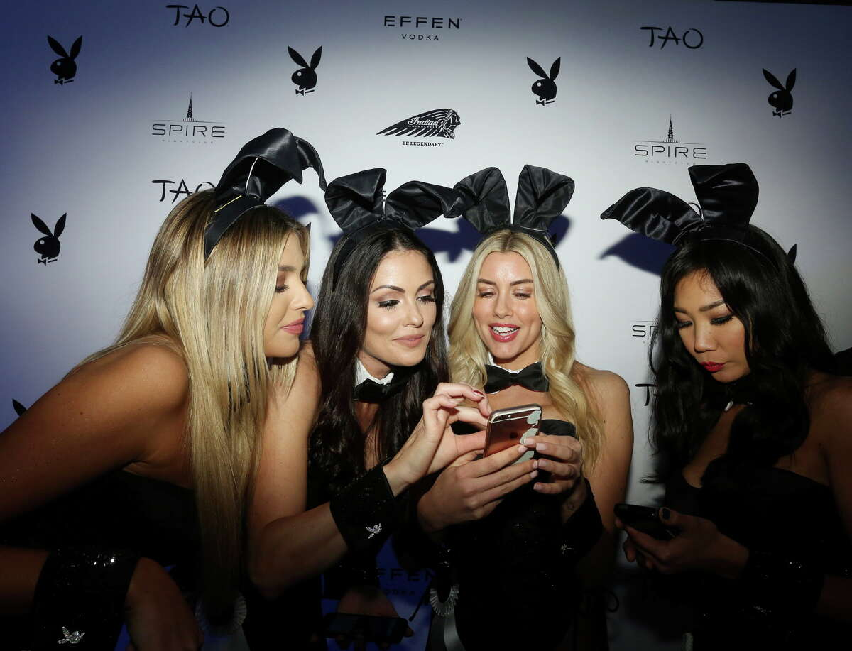 Playmates Monica Simms, from left, Summer Altice, Heather Rae Young and Hiromi Oshima poses look at a selfie on the red carpet at the Playboy party, Saturday, Feb. 4, 2017, in Houston.