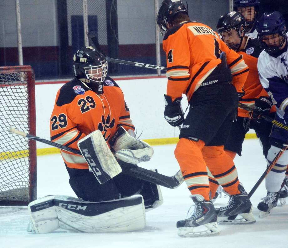 Edwardsville goalie Matt Griffin, left, hangs on to make save with defenseman Jared Nosser shielding him from CBC during the first period in Affton, Mo.