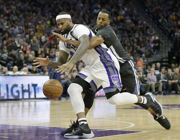 Sacramento Kings forward DeMarcus Cousins, left, and Golden State Warriors forward Andre Iguodala scramble after the ball during the second half of an NBA basketball game Saturday, Feb. 4, 2017, in Sacramento, Calif. The Kings won in overtime 109-106. (AP Photo/Rich Pedroncelli)