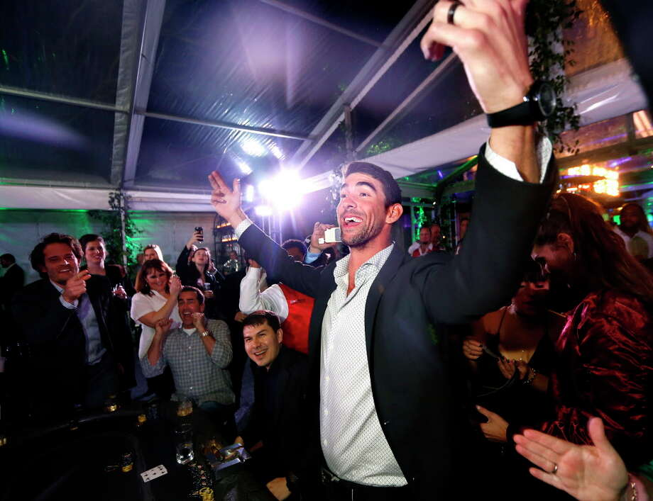 "Olympian Michael Phelps celebrates a winning hand during The Giving Back Fund's 8th annual ""Big Game, Big Give"" at Michael and Lisa Holthouse's home on Saturday, Feb. 4, 2017, in Houston. (Annie Mulligan / Freelance) Photo: Annie Mulligan, Annie Mulligan / For The Houston Chronicle / @ 2017 Annie Mulligan & the Houston Chronicle"