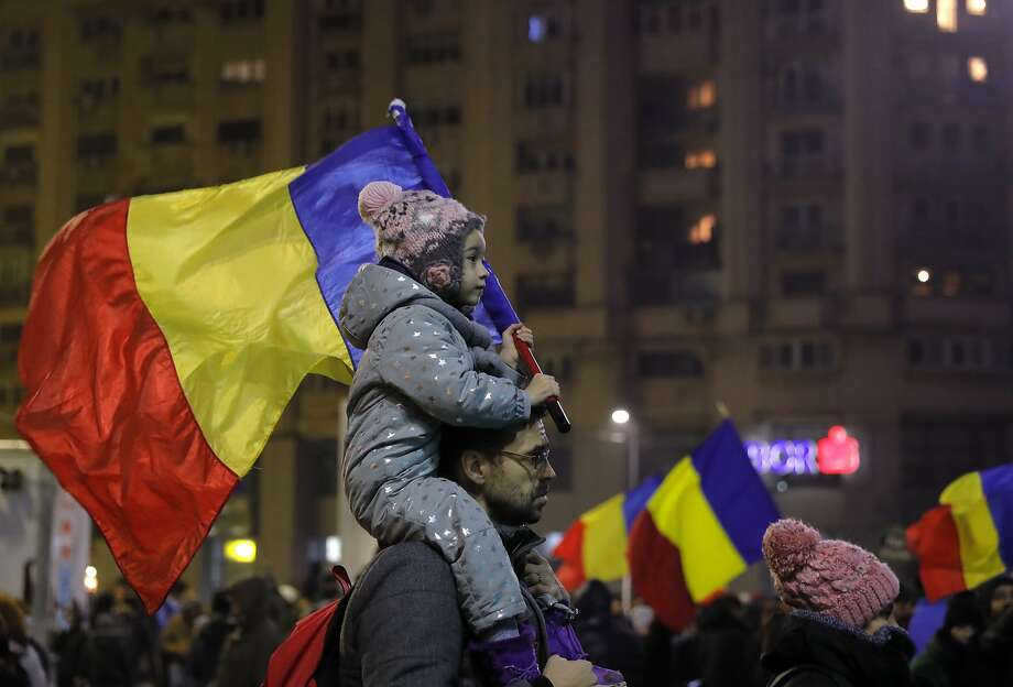 A child carries the Romanian flag during a rally in Bucharest. The government repealed a decree that decriminalized official misconduct, a law that prompted major protests. Photo: Vadim Ghirda, Associated Press