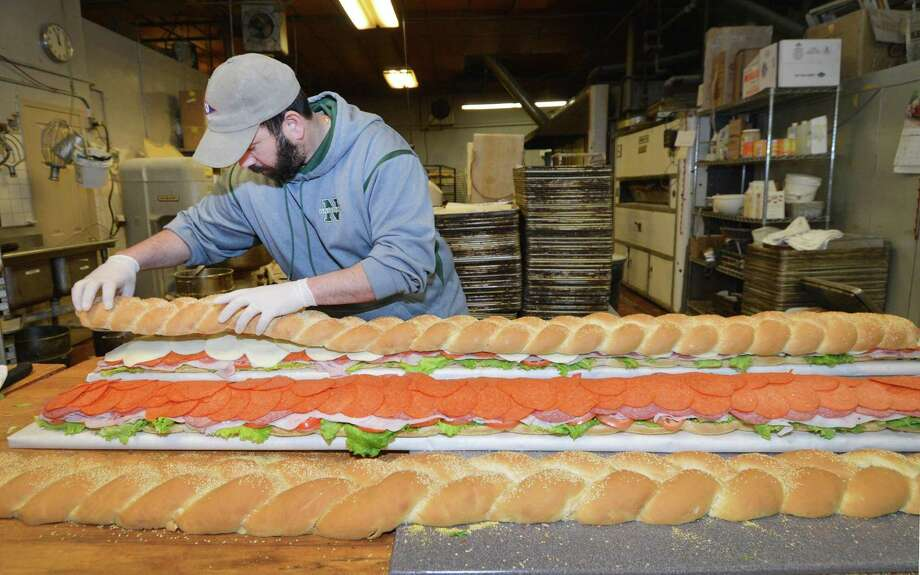On Super Bowl Sunday, Brian Muro works on preparing two 6-foot Italian combo subss for a customer at Muro's New York Bakery and Deli on Main Ave on Sunday. Brian, a third generation co-owner at the family run business uses about 10 pounds of salami, ham, peperoni, provolone and lettuce placed on a special handmade braided roll that are baked early in the morning. Each sandwich will be sliced to feed about 35 people at a Super Bowl party, and along with their four different styles of chicken wings, stromboli bread, and antipasto plates. Customers who pre ordered for this years biggest football game wont be hungry. Photo: Alex Von Kleydorff / Hearst Connecticut Media / Connecticut Post