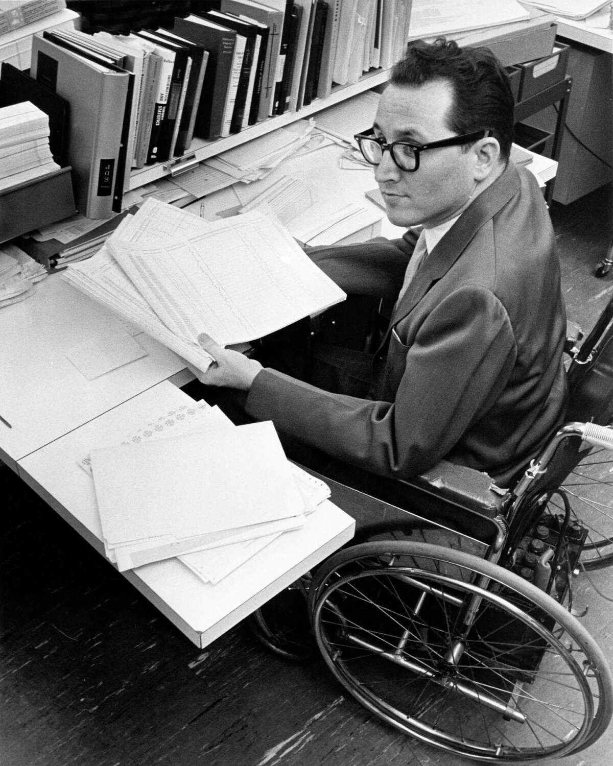 01/1963 - Morris Burns Jr., assistant to the director of the Biomathematics Research Laboratory at Baylor College of Medicine, holds computer printout results for patients at the Texas Institute for Rehabilitation and Research in Houston.