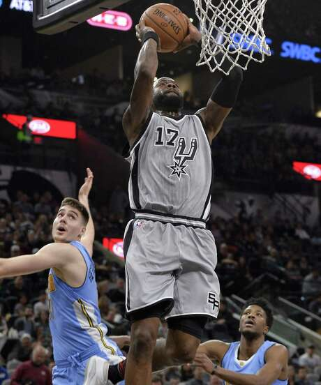 San Antonio Spurs forward Jonathon Simmons (17) dunks as Denver Nuggets' Juancho Hernangomez, left, of Spain, and Malik Beasley look on during the second half of an NBA basketball game, Saturday, Feb. 4, 2017, in San Antonio. San Antonio won 121-97. (AP Photo/Darren Abate) Photo: Darren Abate, FRE / Associated Press / FR115 AP