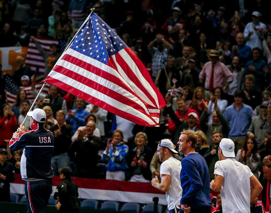 U.S. Davis Cup players John Isner (carrying the American flag), Jack Sock, Sam Querrey, and Steve Johnson celebrate their defeat of Switzerland. Photo: Butch Dill, Associated Press