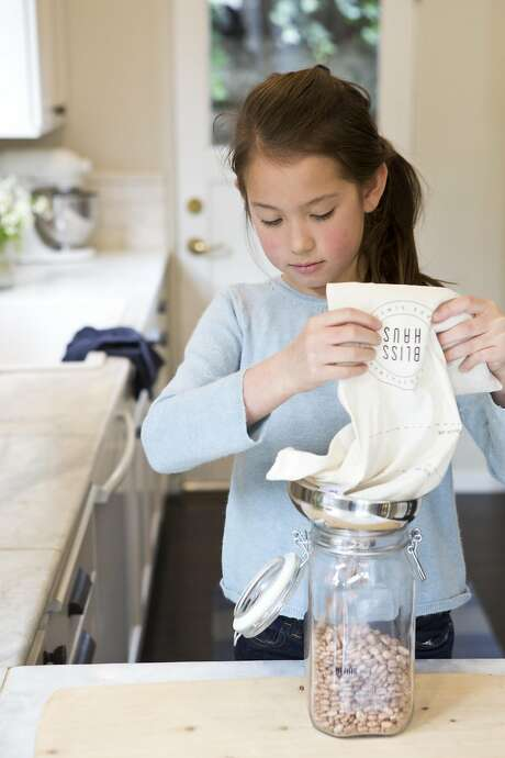 Josie Liu, 9, pours bulk beans from a Blisshaus bag into a Blisshaus jar. Photo: Vivian Johnson, Special To The Chronicle