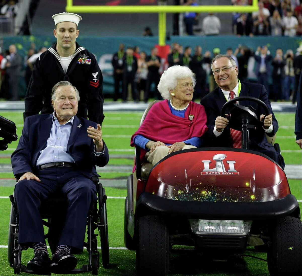 Former President George H.W. Bush and wife, Barbara, wave as they arrive on the field for a coin toss before the NFL Super Bowl 51 football game between the Atlanta Falcons and the New England Patriots Sunday, Feb. 5, 2017, in Houston. (AP Photo/David J. Phillip)