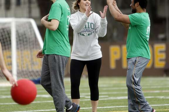 Megan McClain is congratulated after making a catch during a weekly co-ed kickball game organized by The League dating app in San Francisco, Calif., on Sunday, February 5, 2017.