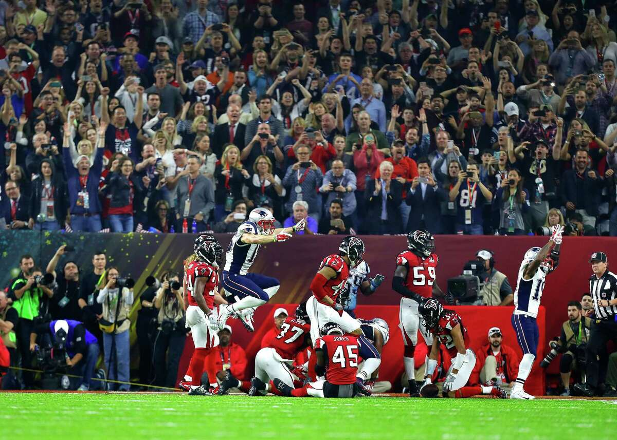 While the Patriots jump for joy as the winning touchdown is scored in overtime, their Falcons counterparts slump to the ground in dejection Sunday night at NRG Stadium.