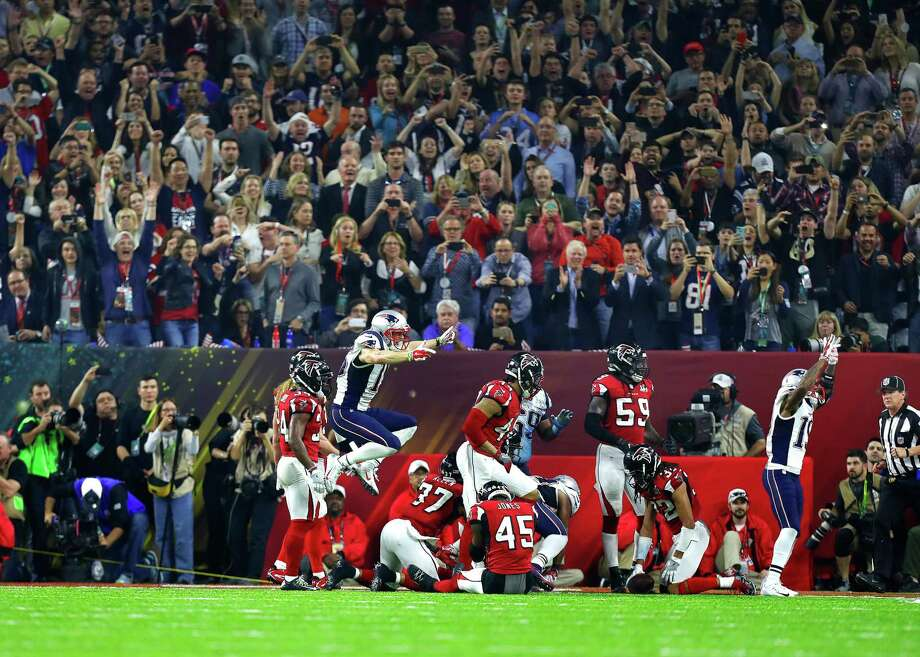 While the Patriots jump for joy as the winning touchdown is scored in overtime, their Falcons counterparts slump to the ground in dejection Sunday night at NRG Stadium. Photo: Karen Warren, Staff Photographer / 2017 Houston Chronicle