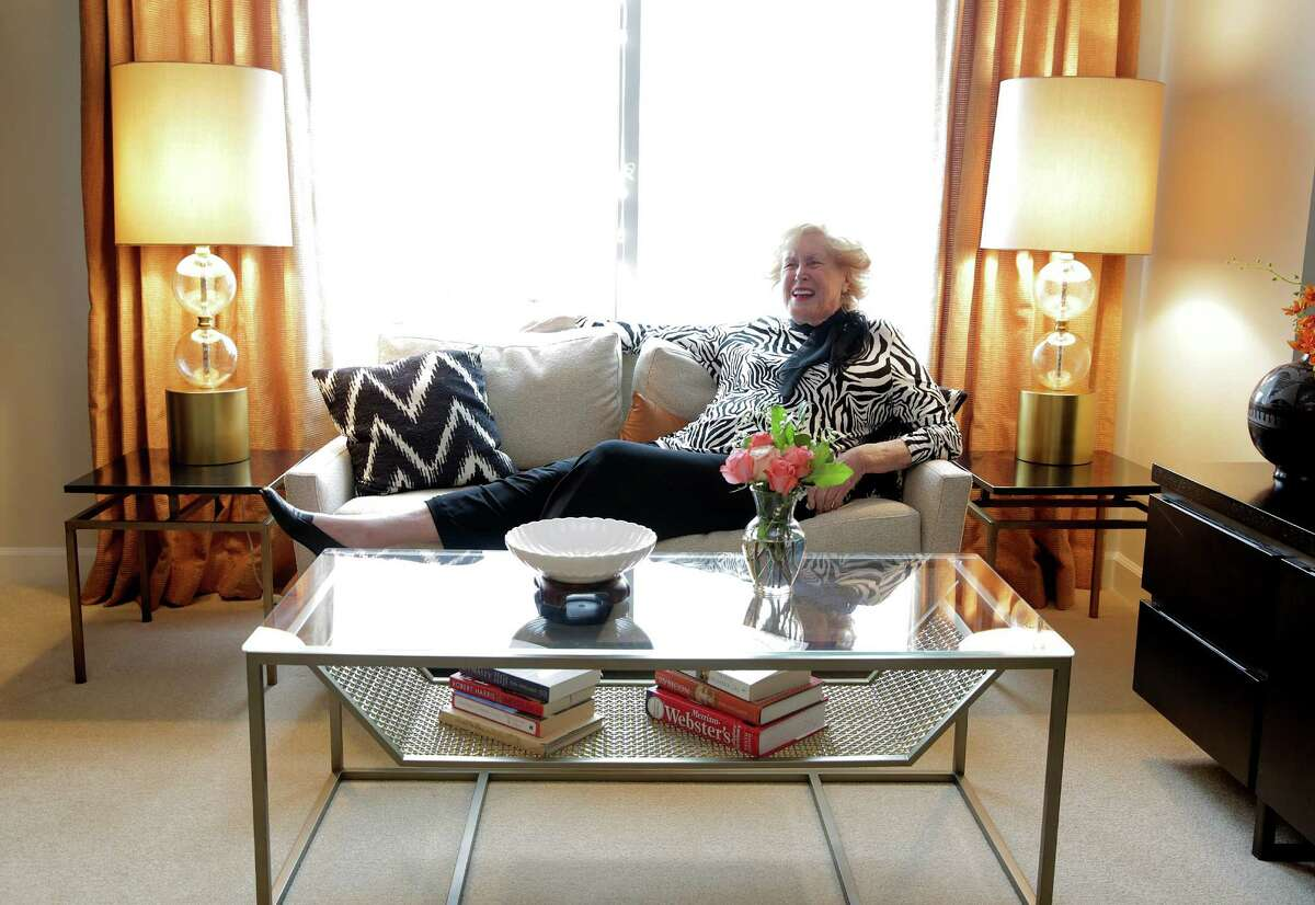 Margaret Paff poses on her chic new sofa, framed by soft curtains and sophisticated lamps. Her coffee table has a shelf underneath, adding storage space and helping the top look less cluttered.