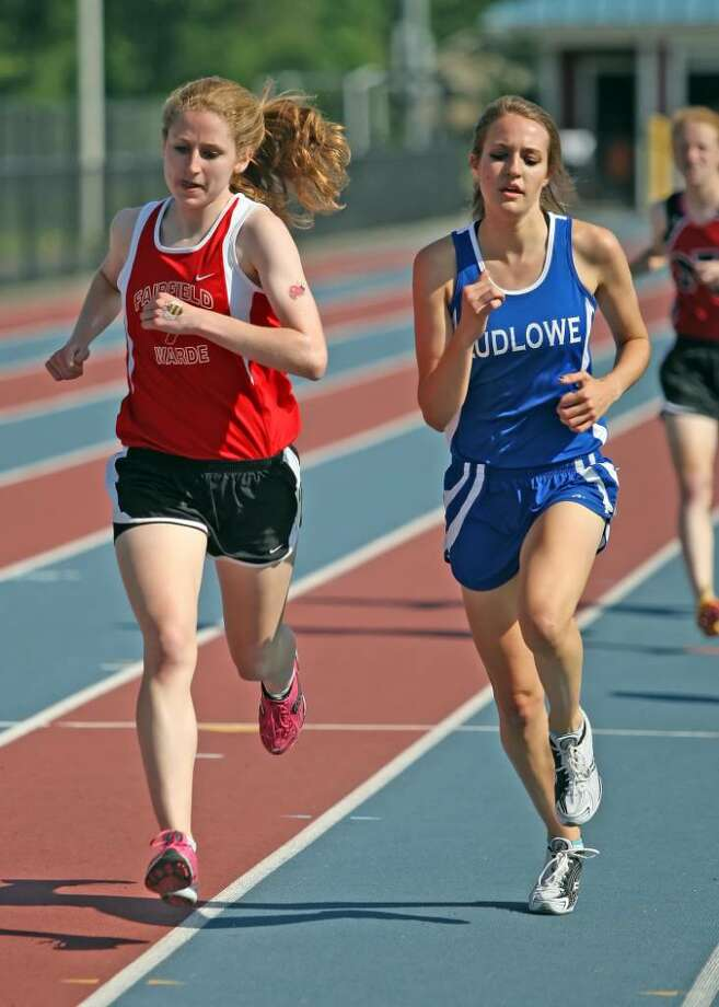 Fairfield Warde's Meg Ryan, left, duels for position with Ludlowe's Heather Moriarty in the 1600m race at the FCIAC Championship meet on Tuesday in Danbury. Photo: Todd Kalif, Todd Kalif For The Fairfield Citizen