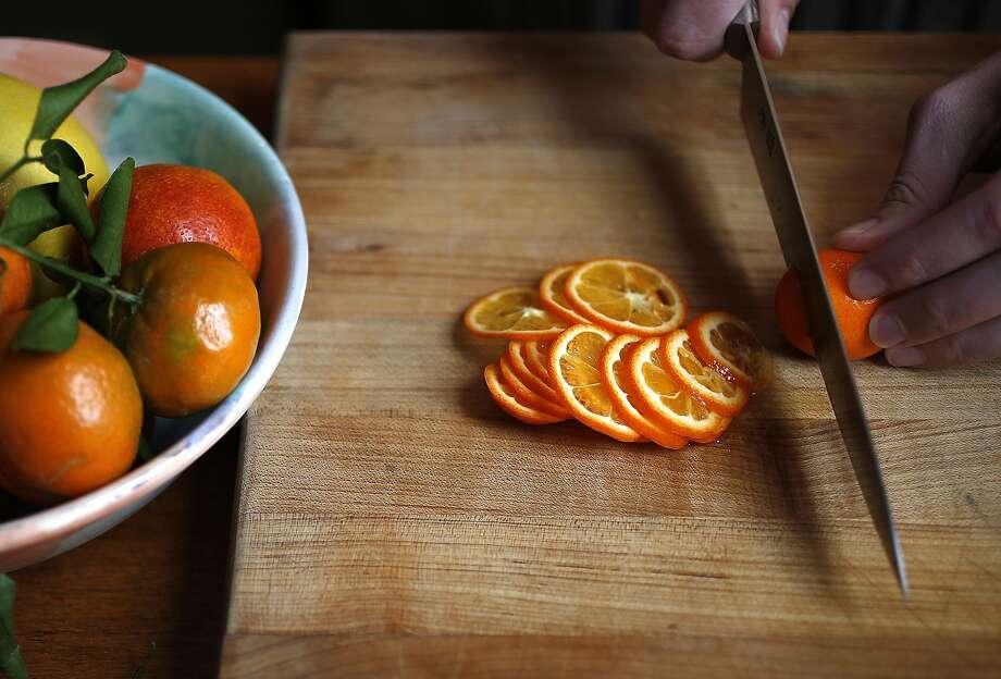 Thinly slice the kumquats and/or mandarinquats into rounds. Photo: Liz Hafalia, The Chronicle