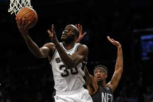 San Antonio Spurs center Joel Anthony (30) drives to the basket past Brooklyn Nets forward Chris McCullough during the second half of an NBA basketball game Monday, Jan. 23, 2017, in New York. The Spurs won 112-86. (AP Photo/Adam Hunger)