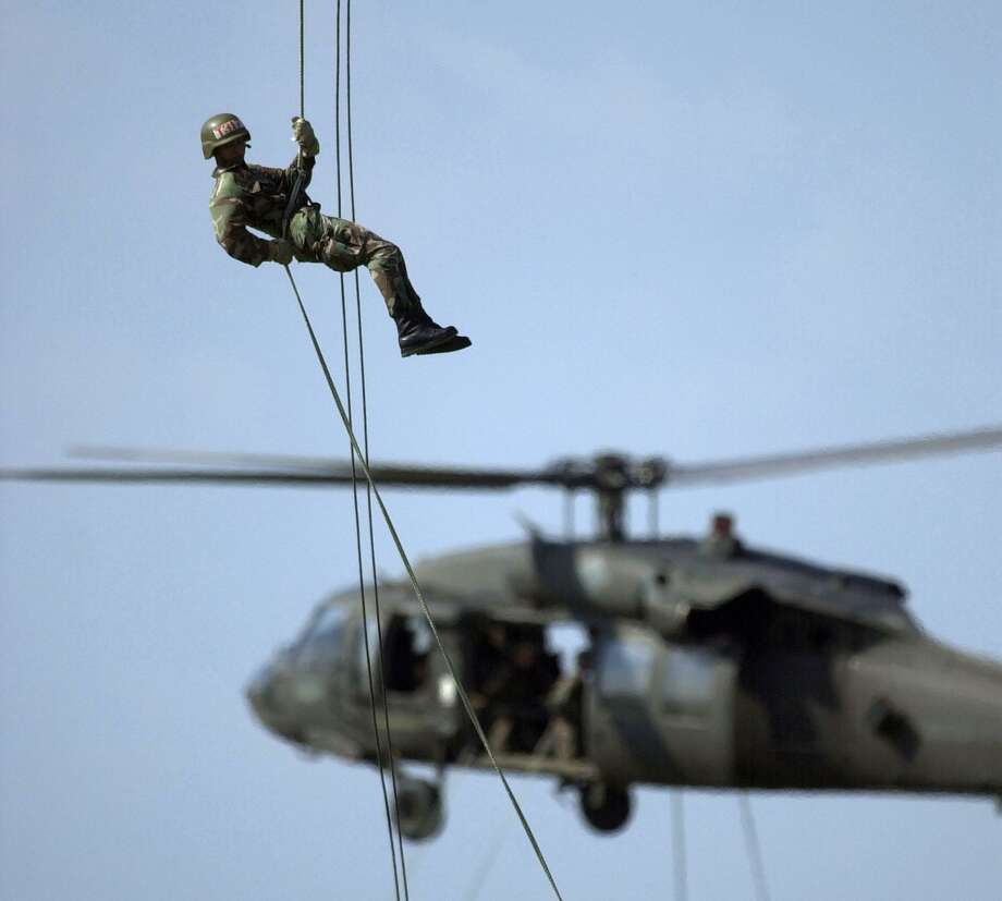 A soldier in the Air Assault School at Fort Campbell, Ky., rappels from one Blackhawk helicopter as a second one carries soldiers in the background, Thursday, Sept. 20, 2001. (AP Photo/Mark Humphrey) Photo: MARK HUMPHREY, STF / AP / AP