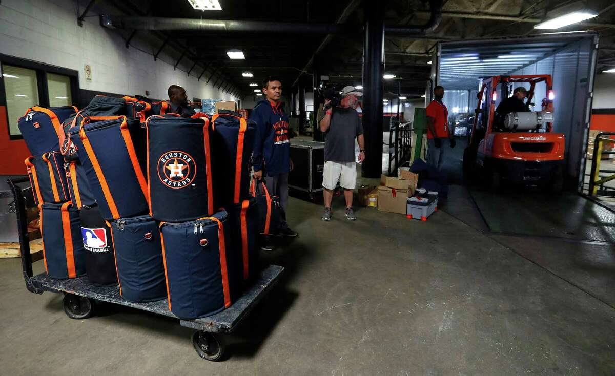 Houston Astros Javier Bracamonte pushes a cart loaded with baseball bags onto a moving truck as the Astros clubhouse staff packed up for spring training in West Palm Beach, at Minute Maid Park Monday, February 6, 2017.