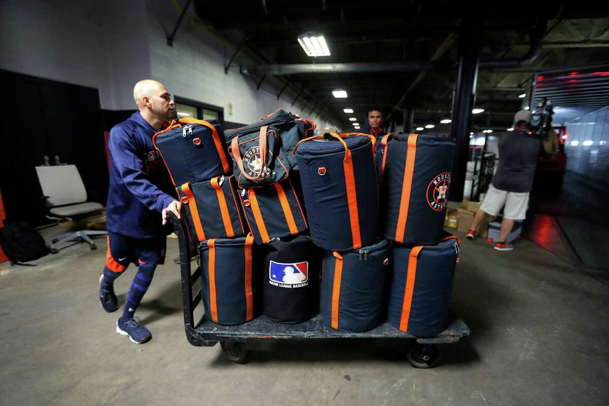 Houston Astros' Javier Bracamonte pushes a cart loaded with baseball bags onto a moving truck as the Astros clubhouse staff packed up for spring training in West Palm Beach, at Minute Maid Park Monday, February 6, 2017.