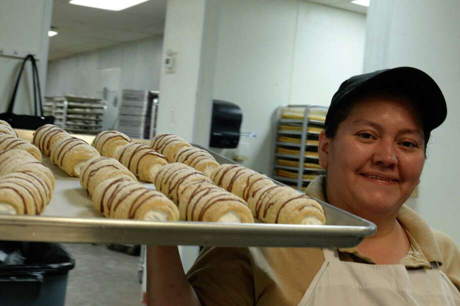 "Sandra Guerra takes a tray full of pastries she has prepared to the front at the El Bolillo bakery  on Wayside in Houston.  El Bolillo plans to open its largest location this spring in Pasadena across the street from the former Pasadena Town Square Mall. The bakery will have an open-concept layout. ""We try to make it an experience,"" owner Kirk Michaelis says."
