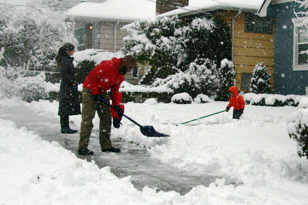 The House family shovels snow in front of their house in West Seattle Monday morning. Several inches of snow fell across the Puget Sound region Sunday night and Monday morning, making for slow roads and plenty of work for residents clearing cars and shoveling sidewalks.