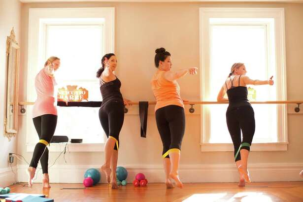 L_R: Ashley Murphy, instructor Renée Taliana, Christina Halstead, Pauline Cusick use resistance loops during a class at Staccato Barre.