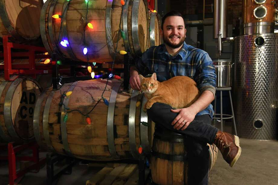 John Curtin, sits with Cooper, the famous distillery cat, at the Albany Distillery on Thursday, Dec. 22, 2016 in Albany, N.Y. (Lori Van Buren / Times Union) Photo: Lori Van Buren / 20039209A
