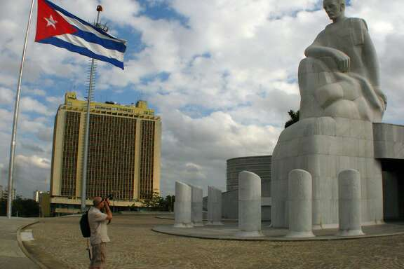 A tourist takes a photo of the Jose Marti statue in Plaza de la Revolucion. The museum tower behind the statue is 358 feet tall, the highest point in Havana, Cuba.