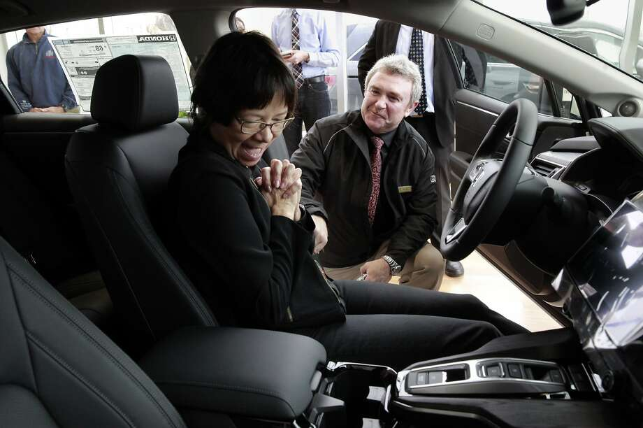 Heather Mc Laughlin, of San Ramon, takes delivery of its first of its kind hydrogen fuel-cell cars the Honda Clarity with the help from Mark Burda, the Clarity brand ambassador, at Dublin Honda,  on Monday Feb. 6, 2017, in Dublin, Ca. Photo: Michael Macor, The Chronicle