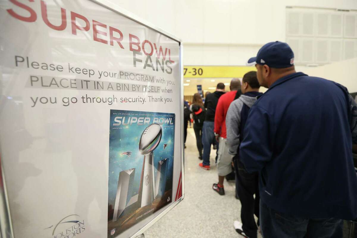 Super Bowl fans holding offical programs we instructed to take the programs out of their checked luggage at Bush International Airport Monday, Feb. 6, 2017, in Houston. ( Steve Gonzales / Houston Chronicle )