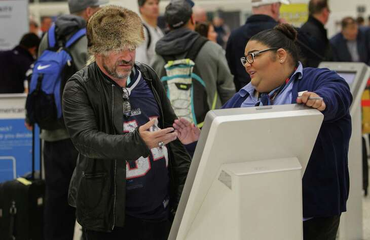 Patriots fan Mike Briller of Los Angeles, who attended Super Bowl LI, stayed up and then went to IAH for an early flight Monday, tries to navigate self check-in with help from American Airlines' Vivian Torrech.