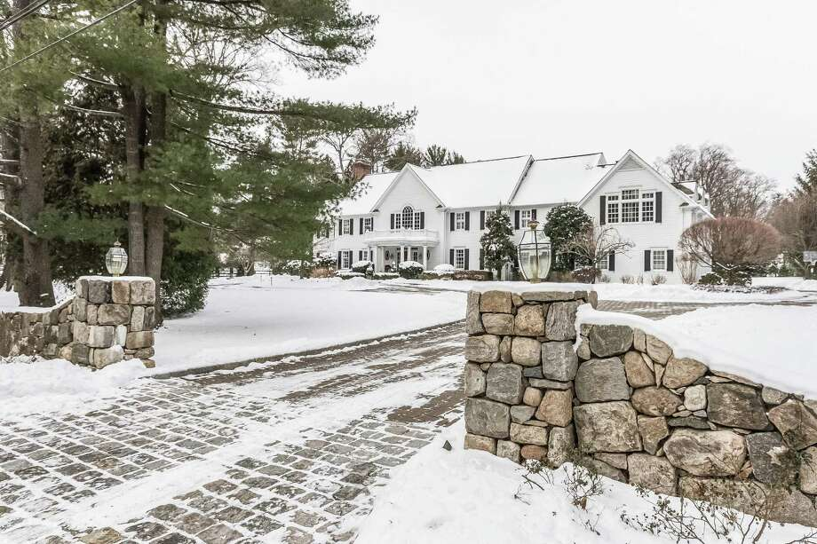 A fieldstone wall lines the front of this property at 5 Peach Hill Road and fieldstone pillars topped with lanterns mark the entrance to the circular driveway. Photo: PlanOmatic / © 2017 PlanOmatic