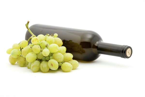 wine bottle and white grapes studio isolated
