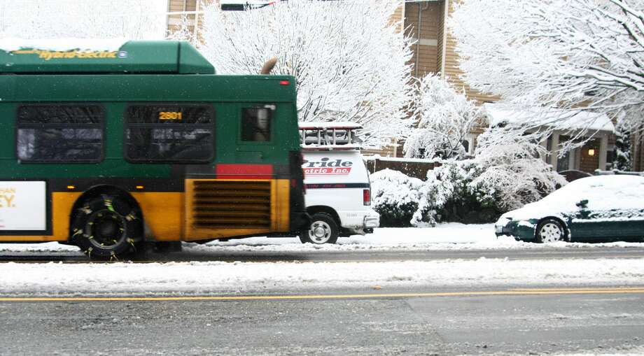 The number 21 Metro bus heads north along 35th Avenue SW Monday morning, chained up for traction in the snowy weather. Several inches of snow fell across the Puget Sound region Sunday night and Monday morning, making for slow roads and plenty of work for residents clearing cars and shoveling sidewalks. Daniel DeMay/Seattlepi.com Photo: DANIEL DEMAY/SEATTLEPI.COM